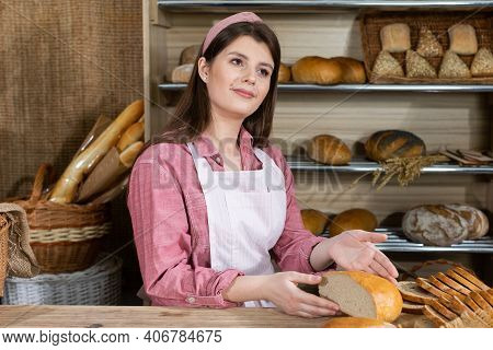 The Saleswoman Holds A Cut Half Of The Round Bread In Her Hand And Shows It To Everyone. Attractive