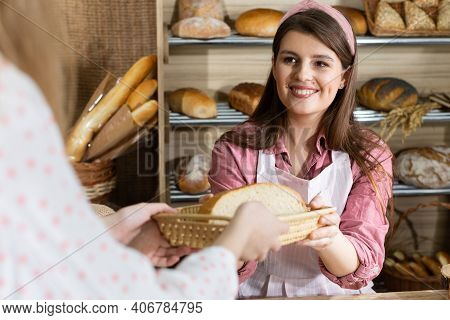 After Paying For The Bread, An Attractive Saleswoman Serves Half A Loaf Of Bread To A Young Customer