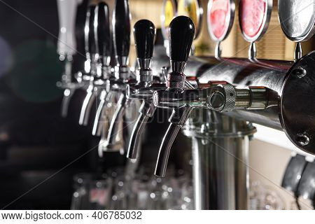 A Row Of Beer Taps In A Beer Bar Close-up. Beer Bottling In The Restaurant. The Bar Counter.