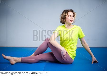 Young Sporty Woman Stretching Legs Before Exercise At Gym. Fit Class Exercising Stretching And Warmi