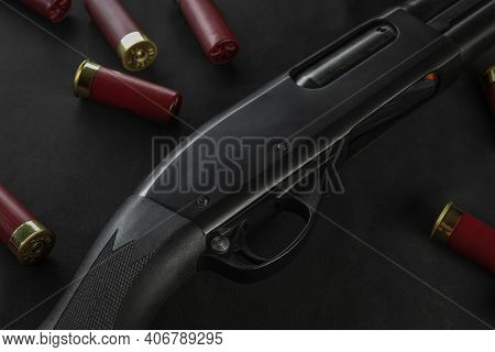 A Close Up Detailed View Of A Pump-action 12 Gauge Shotgun Is Laid Flat On A Black Surface.  Red Sho