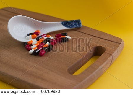 Assorted Pharmaceutical Medicine Pills Spilled From Porcelain Spoon Placed On A Chopping Board With
