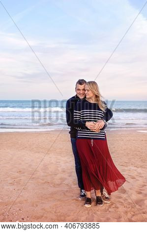 Loving Couple On The Beach With Sea Background. Love, Devotion And Affection In His Gentle Hugs
