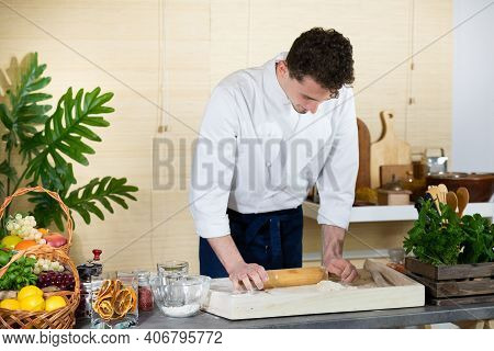 In The Final Stage Of Making The Pizza Dough, A Handsome Chef Rolls The Raw Dough Lying On The Dough