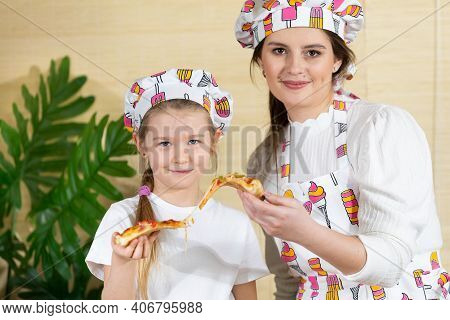 A Proud Mother And A Five-year-old Daughter Take A Portrait Photo Of Themselves After Baking A Pizza