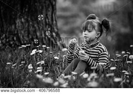 Lovely little five-year girl blowing soap bubbles in the park. Black and white photo.