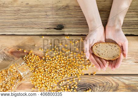 Young Hands Protectively Hold One Slice Of Wheat Bread. Wooden Background With Scattered Corn Kernel