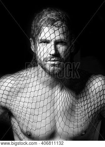 Man Wears Mask Of Black Fishnet Stocking On Face On Dark Background With Bare Muscular Chest. Sexy G