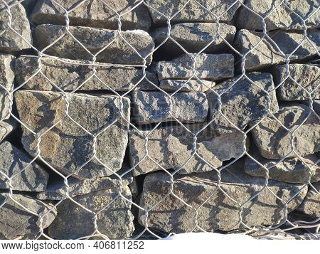 Fence Made Of Gabions, Rock Fence. Texture Of The Gabion Fence Is Made Of Natural Stone And Metal Me
