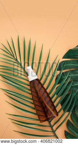 Suntan Lotion Bottle On Soft Orange Background With Tropical Leaf. Top View, Copy Space. Sun Protect