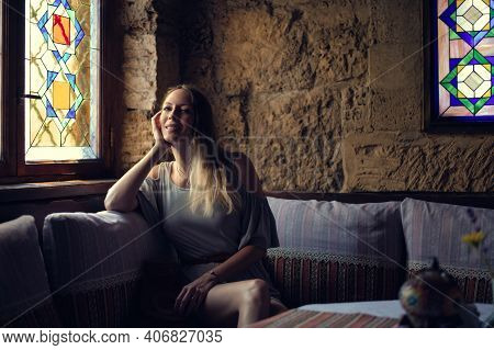 Portrait Of Young Beautiful Woman In Asian Restaurant Sitting On The Sofa