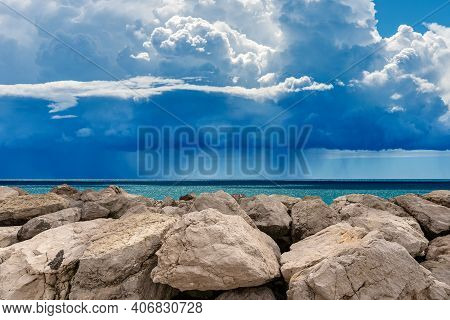 Cumulus Clouds (cumulonimbus) On Blue Sky With Torrential Rain Over The Mediterranean Sea With Break