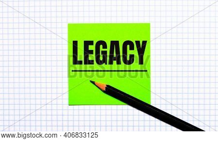 There Is A Green Sticker With The Text Legacy And A Black Pencil On The Checkered Paper.