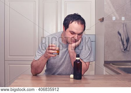 A Man Looks Thoughtfully At A Bottle Of Alcohol Sitting In The Kitchen With A Glass In His Hand. Pro