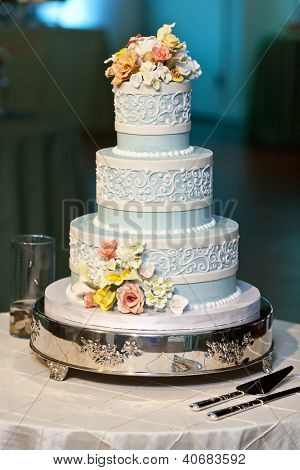 three tiered blue and white wedding cake with confectionery roses