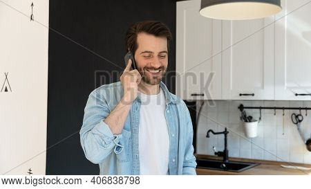 Happy Millennial Male Involved In Pleasant Phone Conversation At Kitchen