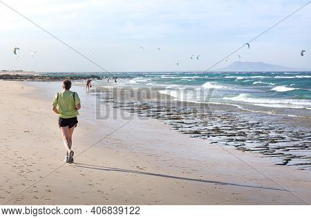Fuerteventura, Spain - May 10, 2013. Mature Man Jogging On A Beach With Kite Surfers In The Backgrou