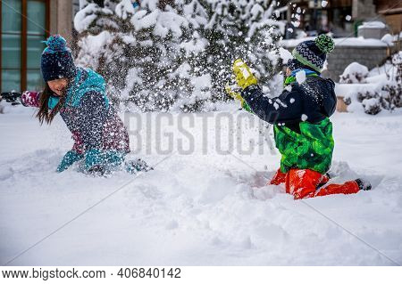 Children Playing With Snow. Two Asian Children In Ski-wear Throwing Snow In Winter. Happy Childhood