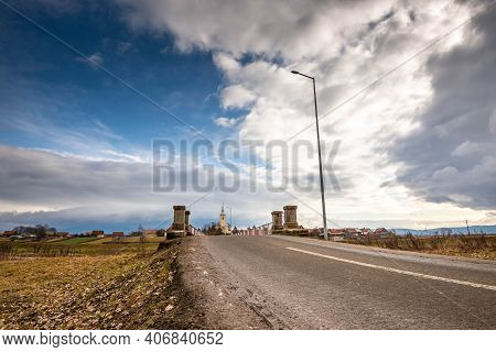 Santimbru, Romania- 06 February 2021: Bridge Over Olt River Built In 1980, Local Catholic Church In