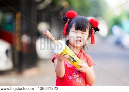 Young Girl Dressed In Chinese Cheongsam Qipao Clothing. Happy Child Imaginative Used A Yellow Umbrel