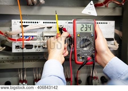 Electrician With A Multimeter In Hands Measures Voltage In The Electrical Box.