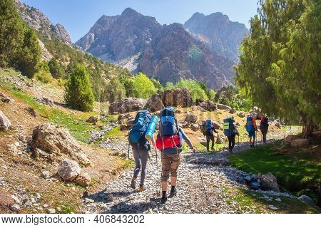 Hikers With Backpacks Walking In Mountains. Group Of Friends In Fann Mountains, Tajikistan. Mountain