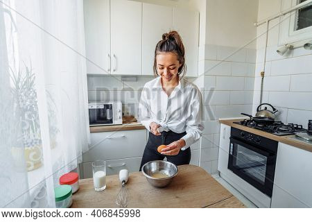 A Young Beautiful Woman In White Clothes Is Preparing To Cook In The Kitchen, Breaking Egg In Bowl.