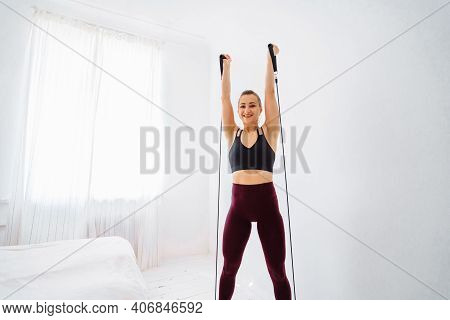 Muscular, Attractive, Beautiful Blonde Fitness Trainer Doing Home Exercises With A Black Expander. S