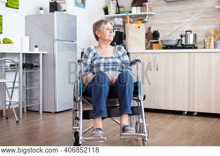 Portrait Of Disabled Unhappy Senior Woman In Wheelchair Looking Lost In Kitchen. Elderly Handicapped