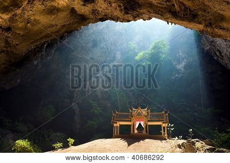 Morning sunbeam on golden buddhist pavilion in wild cave, Sam Roi Yot, Thailand