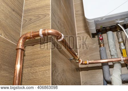 Copper Pipes For Natural Gas Installations, Attached To A Wall In A Boiler Room Lined With Ceramic T