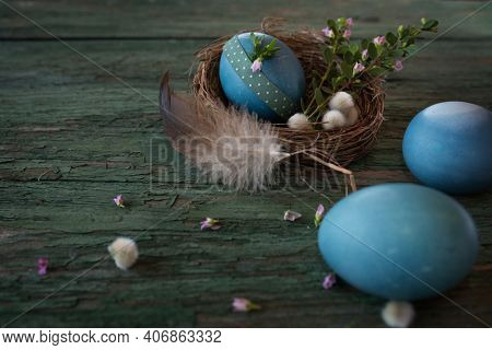 Happy Easter Decoration In Country Style With Blue Easter Eggs In A Nest And Smal Flowers On Weather