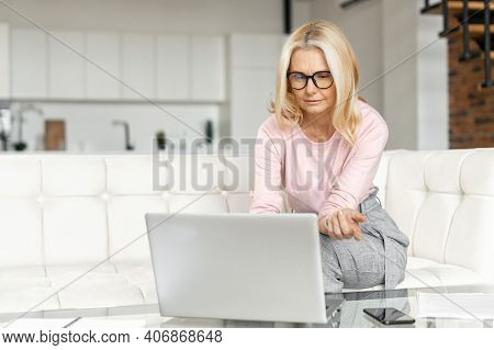 Brooding Middle-aged Woman Using A Laptop For Remote Work At Home, Studying Online, A Serious Female
