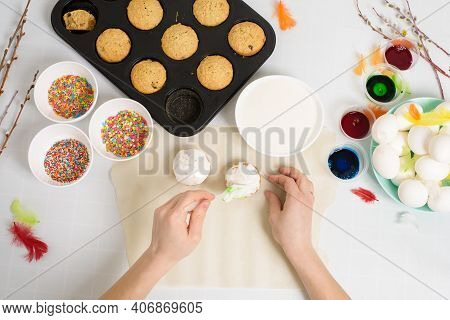 The Process Of Decorating Mini Cupcakes Easter Cakes With White Icing And Sweet Candies, Top View, W