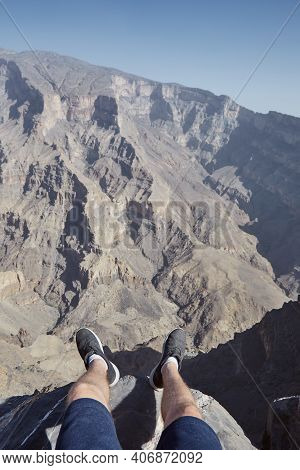 Young Man Resting At The Edge Of Cliff. Personal Stunning View With Canyon, Jebel Shams In Oman