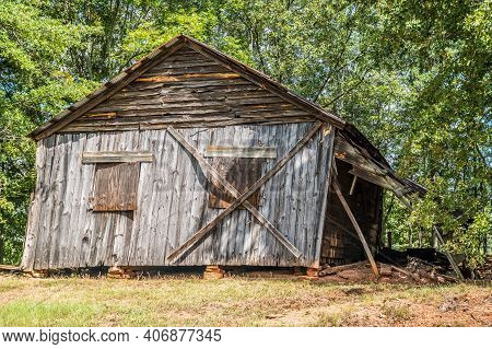 Abandoned Old Wooden Farmhouse Collapsing From Neglect And Time Boarded Up And Falling Off The Stone