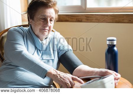 Caucasic Woman Over 70 Checking Her Blood Pressure At Home Near The Window.short Hair, Blue Sweater