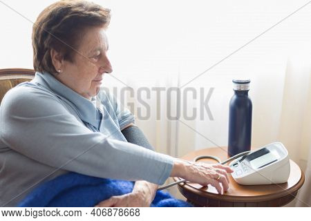 Caucasic Woman Over 70 Checking Her Blood Pressure At Home With A Digital Monitor. Short Hair, Blue