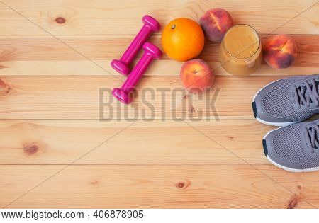 Homemade Healthy Fruits Smoothie Made Of Oranges, Peaches And Bananas, Two Pink Dumbbells, Sneakers,