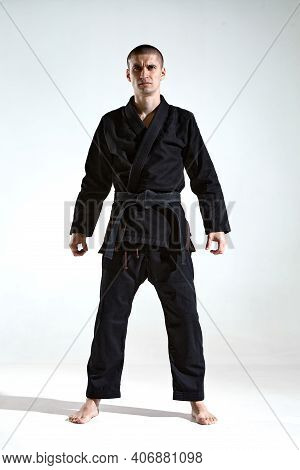 Frowning Guy In Black Kimono Fighter Posing On White Studio Background With Copy Space, Mix Fight Co