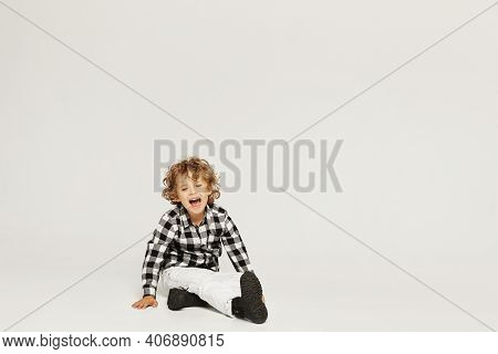 Crying Curly Little Boy Sits On The Floor And Keeping Hand On His Leg. A Small Kid Broke His Leg, Is