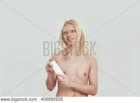 Young Caucasian Man Shaking Long Blond Hair While Holding Shampoo Bottle And Smiling At Camera On Wh