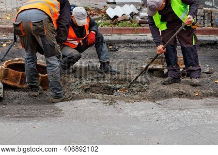 A Team Of Road Service Workers In Reflective Vests Are Repairing A Sewer Hatch On The Roadway. Copy