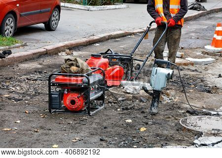 A Road Worker Wearing A Reflective Orange Vest Repairs And Installs Sewers Using A Compactor Plate,