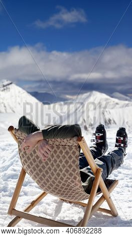 Skier At Snowy Winter Mountains Resting And Basking In Sun After Skiing On Sun-lounger. Caucasus Mou