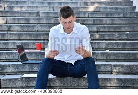 Businessman Sitting On Stairs And Looking On Financial Report. Business And Trade Concept.