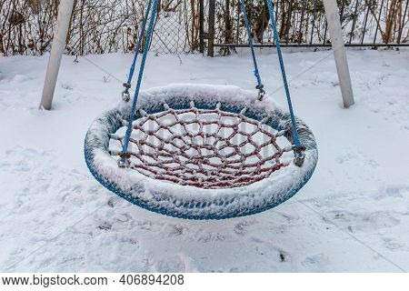 Empty Swing In The Winter Playground