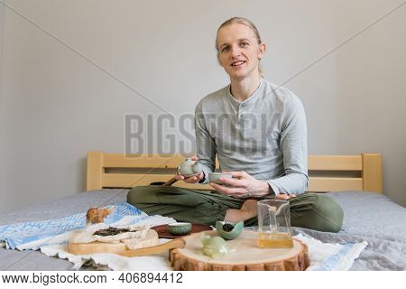 Happy Man Sitting On The Bed, Doing Tea Ceremony Alone, Stay Home And Be Safe During Carantine. Chin