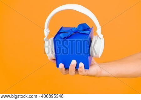 Music Gift Conept. Gift Box With Headphones. Male Hand Hold Present Yellow Backdrop. Modern Headset.