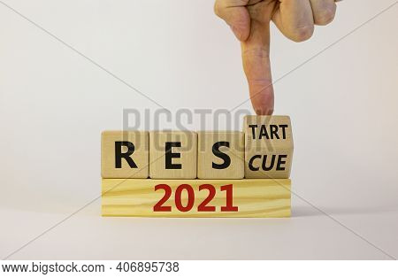 2021 Rescue And Restart Symbol. Businessman Turns A Cube And Changes The Word '2021 Rescue' To '2021